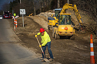 Construction worker clears debris from the roadway before closing down work on Hempstead Rd. at the end of the day.
