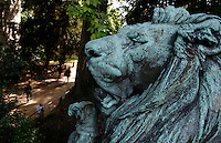 Close up view from above of the statue called Lion de menagerie baillant, un chien entre les pattes (menagerie lion yawning with a dog in his legs), created by Henri Jacquemart circa 1857 and located at the bottom of the Labyrinth in the Jardin des Plantes, Paris, 5th arrondissement, France. In the background, visitors of the Botanical Gardens are walking in a tree-shaded alley of the Labyrinth. This statue by Henri Jacquemart was probably inspired by the famous menagerie lion Woira, a Senegalese lion who was inseparable from his dog companion. Founded in 1626 by Guy de La Brosse, Louis XIII's physician, the Jardin des Plantes, originally known as the Jardin du Roi, opened to the public in 1640. It became the Museum National d'Histoire Naturelle in 1793 during the French Revolution.
