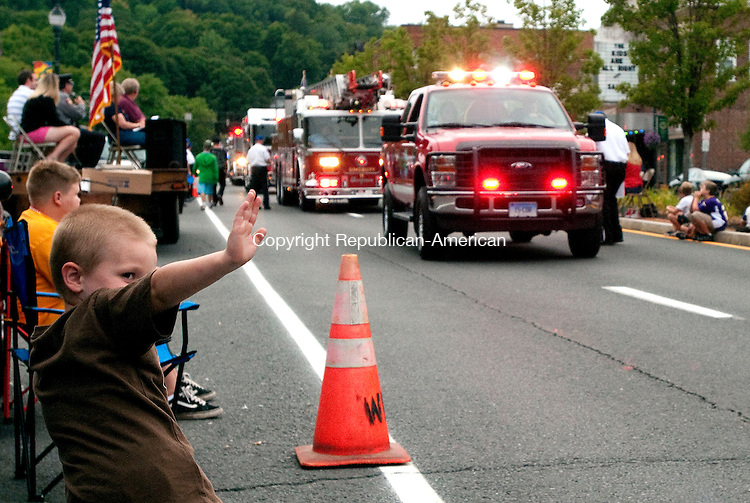 MIDDLEBURY, CT, 21 AUGUST, 2010-082110JS06-Aiden Blanchette, 3, of Torrington waves as fire trucks pass down Main Street during the annual Winsted Fire Department's Firemens Parade in downtown Winsted on Saturday.  The event is part of the department's annual fundraiser carnival. <br /> Jim Shannon Republican-American