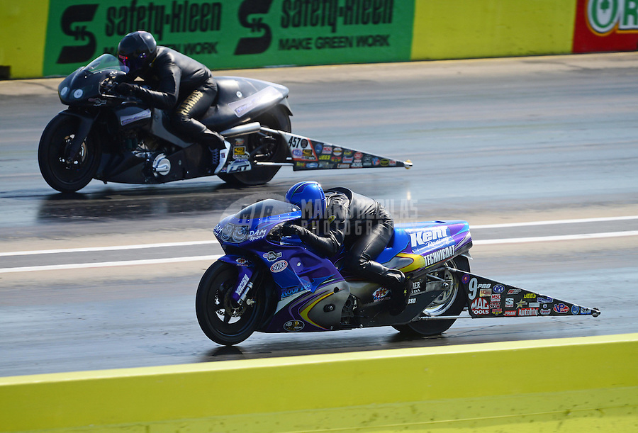 Sept. 22, 2012; Ennis, TX, USA: NHRA pro stock motorcycle rider Michael Phillips (near lane) races alongside Redell Harris during qualifying for the Fall Nationals at the Texas Motorplex. Mandatory Credit: Mark J. Rebilas-
