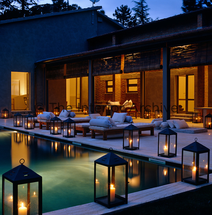 Candlelight from the lanterns surrounding the swimming pool reflects in the calm water on a summer's evening