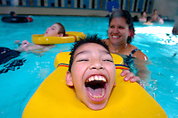 RLuis Duarte has the time of his life swimming in the pool with help of Assistant Aid Angelina Martinez. Luis lights up when he swimming, showing his delight with his huge open mouth smile. Fellow class mate Jacob Riebau floats in the background. Jamie scott lytle photographer