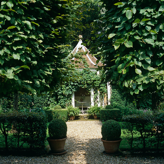 A garden room with a pepper-pot roof is almost hidden from view amongst the foliage of the garden