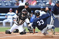 Asheville Tourists catcher Brian Serven (25) fields the ball and prepares to tag out a hard sliding Brandon Wagner (33) as home plate umpire Forrest Ladd prepares to make a call during a game against the Charleston RiverDogs at McCormick Field on July 4, 2017 in Asheville, North Carolina. The Tourists defeated the RiverDogs 2-1. (Tony Farlow/Four Seam Images)