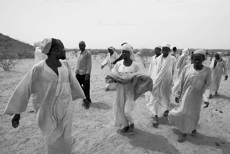 Farchana, Tchad, June 5, 2004.Men carry the body of Hafiz Malik Yaya, 9 months old, dead of severe malnutrition, before burying him. More than 13 thousand Sudanese refugees from Darfur stay in this camp in very harsh conditions.
