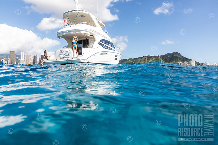 Friends enjoy a lovely day aboard a white power cruiser in the waters of Waikiki, O'ahu, with Diamond Head in the distance.
