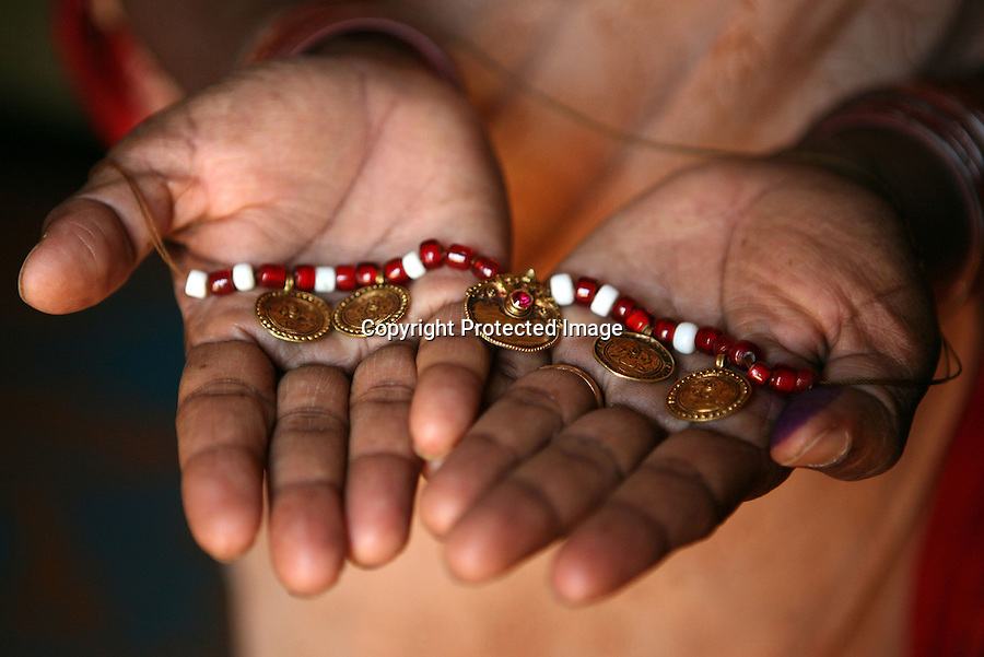 "Vimala Madar, 40, holds her ""muttu"", the red and white beaded necklace tied around her neck during the dedication ceremony performed on her when she was ten years old to convert her into a Devadasi.  During this ceremony, Madar was ""married"" to the Hindu deity, Yellamma, and was then considered one of Yellamma's servants.  From this day on, she was no longer eligible to marry a mortal and had to perform temple duties as well as fulfill the sexual needs of the priests and men in her community.  Madar's mother too was a Devadasi and tradition has it that any girl child of a Devadasi too must become a Devadasi, ensuring a constantly replenished supply of new young Devadasis."