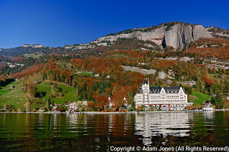 Hotel in autum along shore of Lake Lucerne from sightseeing boat, Lake Lucerne, Switzerland