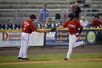 Potomac Nationals manager Tripp Keister (7) congratulates KJ Harrison (12) after hitting a home run during a Carolina League game against the Myrtle Beach Pelicans on August 14, 2019 at Northwest Federal Field at Pfitzner Stadium in Woodbridge, Virginia.  Potomac defeated Myrtle Beach 7-0.  (Mike Janes/Four Seam Images)