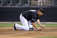 Kannapolis Intimidators manager Justin Jirschele (9) covers home plate with dirt after having been ejected for arguing a call at first base in the bottom of the 9th inning during the game against the Hickory Crawdads at Kannapolis Intimidators Stadium on May 18, 2017 in Kannapolis, North Carolina.  The Crawdads defeated the Intimidators 6-4.  (Brian Westerholt/Four Seam Images)