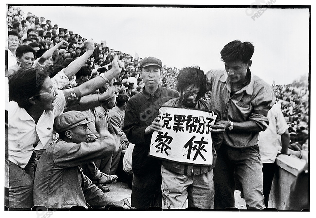 At a mass rally organized by rebels in Provincial People?s Stadium, Party Secretary Wang Yilun and Li Xia, wife of Governor Li Fanwu are denounced, their faces and clothes splattered with ink, and their crimes spelled out on placards around their necks. Harbin, 29 August 1966