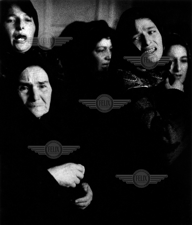 The mother, wife, and sisters of a man killed in the Chechnya war grieve at his funeral. In Chechen culture, men and women must grieve separately. Only men are allowed to go to the graveyard for a man's burial, with women saying their farewells at the family home.