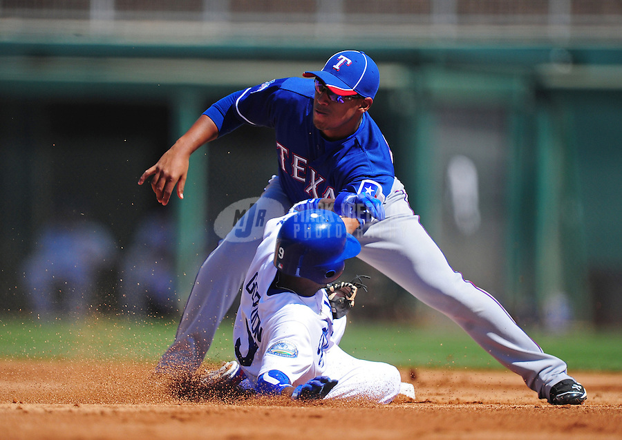 Mar. 16, 2012; Phoenix, AZ, USA; Los Angeles Dodgers base runner Dee Gordon slides into second base where he is tagged out on a stolen base attempt by Texas Rangers second baseman Yangervis Solarte in the first inning at The Ballpark at Camelback Ranch. Mandatory Credit: Mark J. Rebilas-