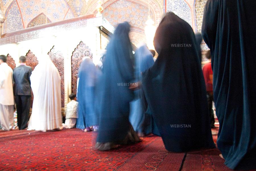 """AFGHANISTAN -  MAZAR-E CHARIF - 7 aout 2009 : .Le nom de Mazar-e Charif signifie """"sanctuaire sacre"""" et fait reference au sanctuaire et a la mosquee qui auraient ete batis, selon les afghans chiites comme sunnites, sur le tombeau de l'imam Ali. Ancien lieu de culte paien puis boudhiste, le sanctuaire de Mazar-e Charif est aujourd'hui le plus grand centre de pelerinage musulman en Afghanistan. Son activite culmine a l'occasion du nouvel an afghan, le 21 mars de chaque annee...Mosquee de Mazar-e Charif. Hommes et femmes se cotoient dans la mosquee. ..AFGHANISTAN - MAZAR-E CHARIF - August 7th, 2009 : The name Mazar-e Charif means """"sacred sanctuary"""" and refers to the sanctuary and mosque which were built, according to Sunni and Shiite Afghans alike, over the tomb of the Imam Ali. An ancient religious site for Pagans and then Buddhists, today the Mazar-e Charif sanctuary is the Muslim pilgrimage centre of Afghanistan. Activity here culminates annually on March 21, Afghan New Year..Mazar-e Charif mosque. Men and women mingle in the mosque."""