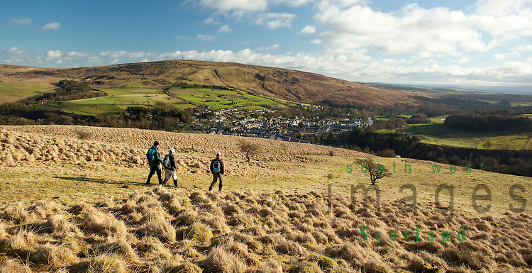Winter walkers walking off Meiklehom Hill lookng down on the town of Langholm on the Scottish border with Whita Hill behind Scotland UK