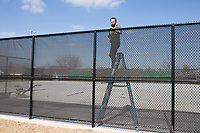 NWA Democrat-Gazette/CHARLIE KAIJO Hunter Horn of Carnahan-White zipties wind screens on a chain link fence, Monday, February 4, 2019 at the new tennis courts at the Bentonville Community Center in Bentonville.<br />