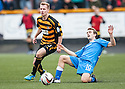 Queen of the South's Daniel Carmichael is bundled off the ball by Alloa's Jonathan Tiffoney.