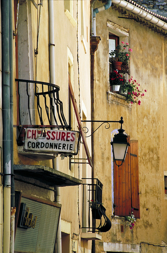 Shop signs, sconce streetlamp and wrought iron balcony rails. Flowerpots on balcony railings and window grill and at bottom of window with closed shutters. Bagnols sur Ceze Provence France.