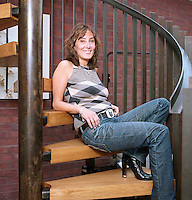 The smiling owner of the house designed by Theis & Khan is photographed relaxing on the steps of the contemporary spiral staircase