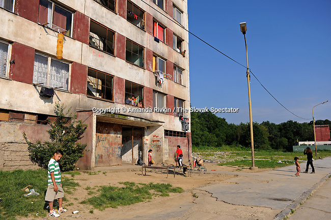 Roma walk beside a building at Lunik IX, a Roma-occupied slum, in Kosice, Slovakia on June 8, 2010. Lunik IX has become a notorious housing complex within Slovakia and the European Union as one of Europe's poorest communities with levels of poverty incomprehensible to most Slovaks.