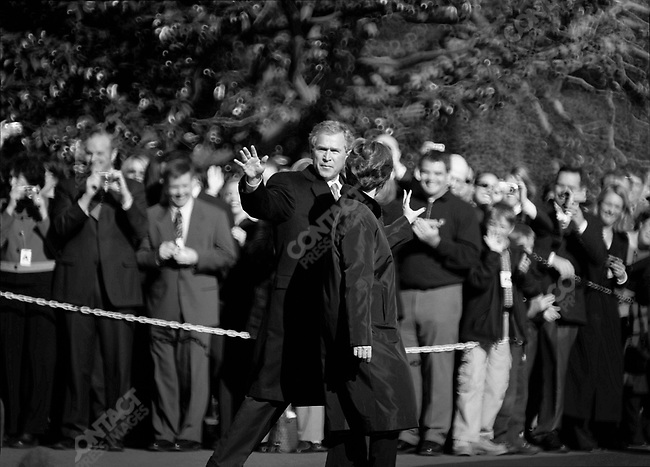 President George W. Bush and his wife, Laura Bush, walk to a helicopter waiting on the lawn of the White House, March 12, 2004.