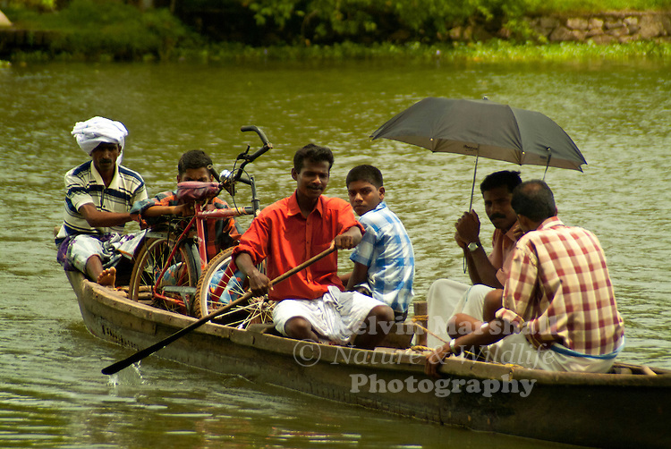 locals from Kerala sitting in a dugout canoe being transported  across the river. Kerala Backwaters, Kerala (Southern India)