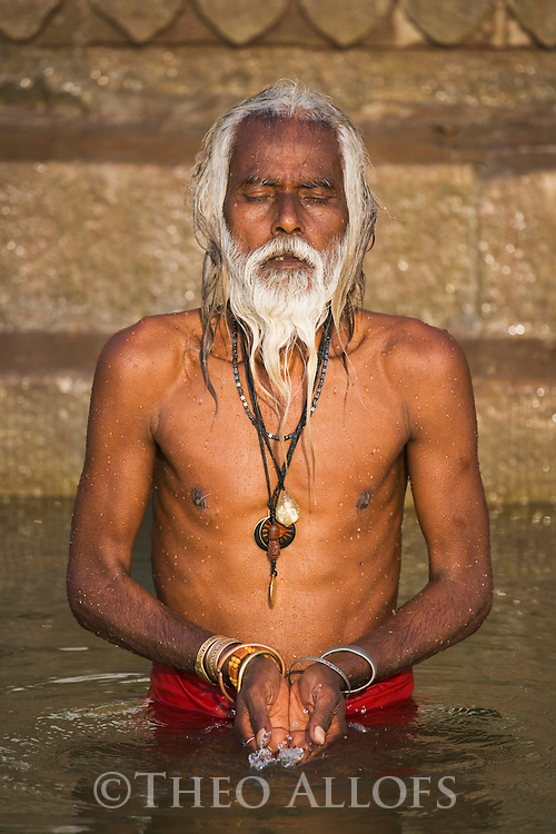 Indian holy man (Sadhu) praying in Ganges River;  Varanasi has been a cultural and religious center in northern India for several thousand years, Varanasi, Uttar Pradesh, India