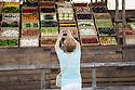 A woman takes picture of the boxes of false vegetables that are part of a set design by Dante Ferretti at Expo 2015, Rho-Pero, Milan, in June 2015.<br /> <br /> Una donna fotografa le cassette di verdura finte che sono parte di una delle scenografie di Dante Ferretti a Expo 2015, Rho-Pero, Milano, giugno 2015.