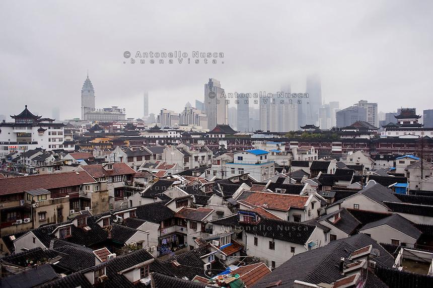 Una veduta di Shanghai che mostra il contrasto tra le vecchie costruzioni e il nuovo che avanza.<br /> View of a section of Old Town and encroaching modern buildings