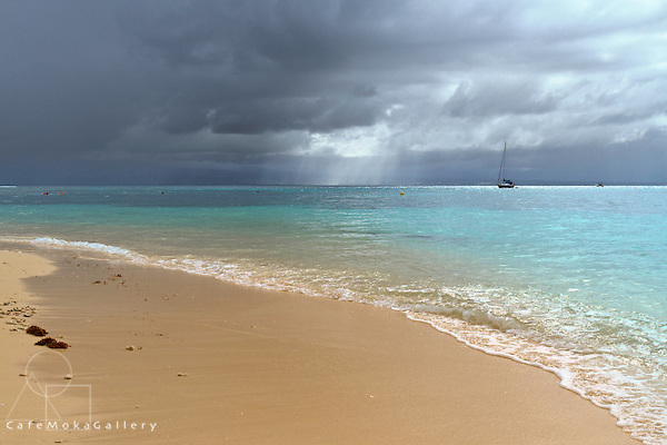 Ilet de Gozier sandy beach, turquoise waters with storm clouds and a yacht in the distance