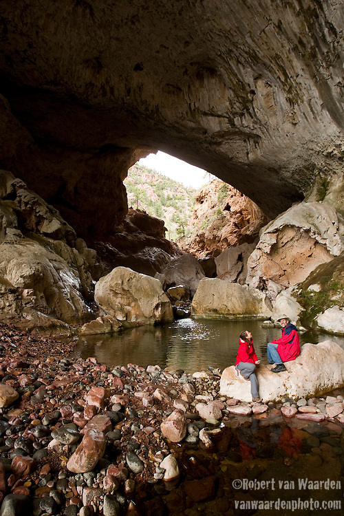 Two Figures take a break under the  massive natural bridge, Tonto, in Arizona