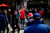 A man sells baseball programs as crowds wait for the beginning of the 2011 season opening game of the Boston Red Sox in Boston, Massachusetts, USA.