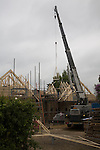 Crane lifting timber roof frame into place on building site, UK