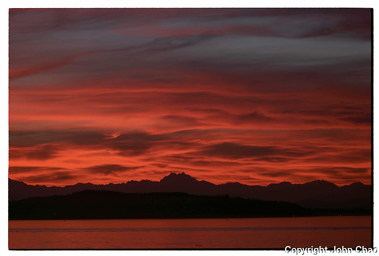 A sunset sky of colorful, layered clouds over Puget Sound and the Olympic Mountain Range, Washington State.