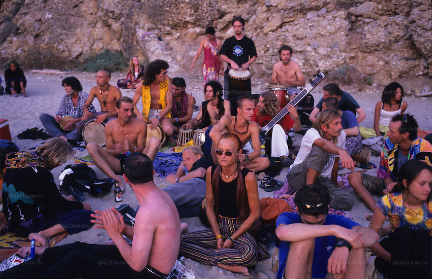 TOURISM CLUBBING, Ibiza. Hippies watching the sunset, beach. Ibiza & Formentera, Baleares islands, Spain, Mediterranean, Europe. Popular holiday resort catering mainly for european tourists. Summer high season, April until September. Well known for 24 hour nightclubbing, package holidays, jet set, all night raves, dancing, techno clubs, drag queens & gay scene, discotheques, speciality theme nights, soapsuds, foam parties, espuma, la mousse. Attractions include shopping, beaches, watersports, boating..