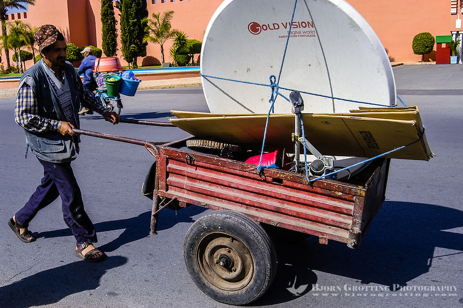 Morocco, Marrakesh. Man with a trolley and satellite dish outside the presidential palace.