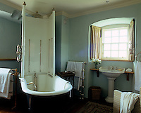 A free-standing Victorian bath tub with a built-in shower unit