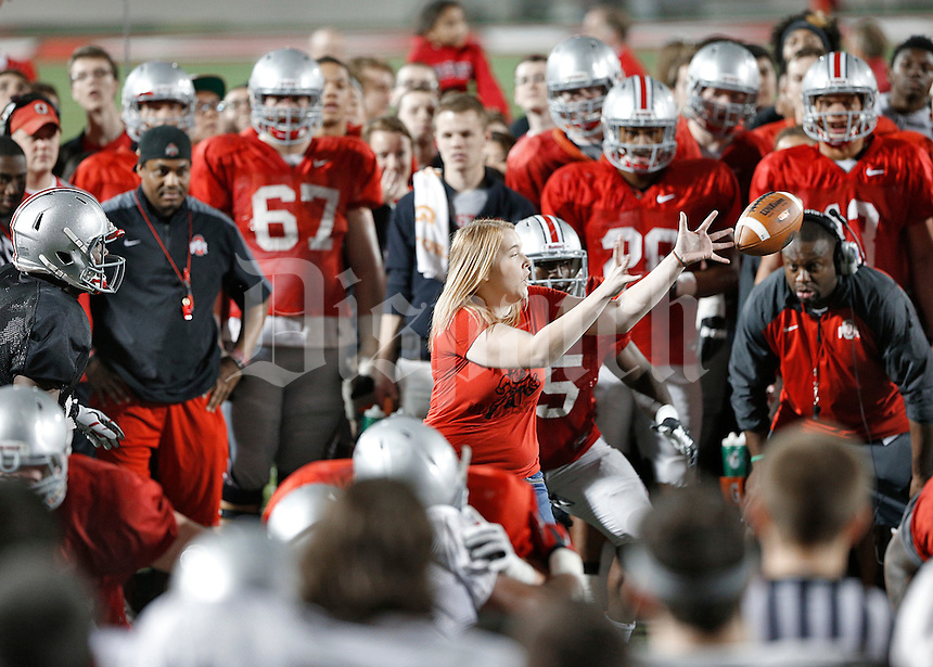 Ohio State University Junior Katie Olinger mishandles a snap from center while getting a chance to participate with Buckeye football team practicing at the Woody Hayes Athletic Center on April 11, 2015. Students were invited to the facility for the fourth annual Student Appreciation Practice .  (Chris Russell/Dispatch Photo)