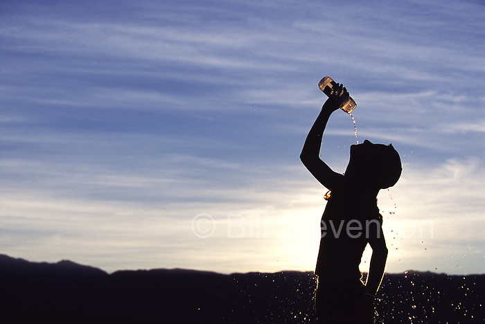 A picture of a female runner cooling down by pouring water onto her head .