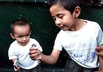 """Un nino en situacion de calle juega con su hermanito en el puente vehicular de Marina Nacional y Melchor Ocampo de la ciudad de Mexico, el 26 de abril de 2002. Los ninos en situacion de calle viven bajo el acoso policiaco de la delegacion Miguel Hidalgo lo que ha provocado accidentes entre ellos al evitar ser arrestados. Muchos de esos ninos son adictos a la """"piedra"""", la cula consiguen a bajo precio y les inhibe las ganas de comer. LA JORNADA/ Heriberto Rodriguez"""