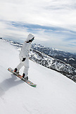 USA, California, Mammoth, a female snowboarder carves her way down a run at Mammoth Ski Resort