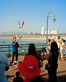 USA, California, Santa Monica, Los Angeles, an entertainer juggles on the Santa Monica Pier with Santa Monica State Beach in the distance