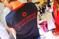 "A wine taster with a black t-shirt tshirt saying ""The Gang of Grenache"" advertising a group of Chateauneuf-du-Pape growers. Rhone. Tasting wine. Ice bucket. France Europe."