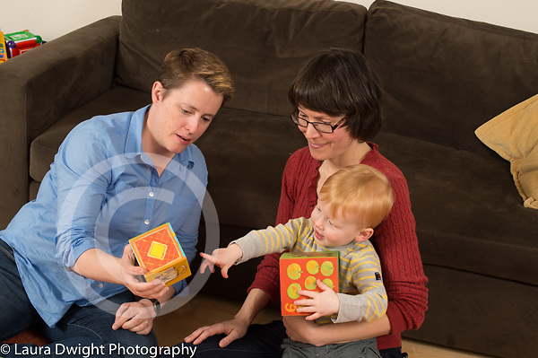 22 month old toddler boy at home with mothers playing with stacking blocks, language development pointing at illustration on block