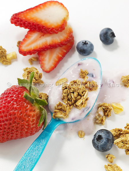 A blue plastic spoon with yogurt, strawberry, blueberries, and granola on a white background