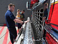 NWA Democrat-Gazette/J.T. WAMPLER Rogers firefighter paramedic Peter Pasquale (LEFT) shows off the hose storage on a firs truck to Dylan Kelley of Rogers and his son Peyton Kelley, 3 during the Rescue Heroes Touch a Truck Experience at Wal-Mart in Rogers. The event were in honor of the return of Fisher-Price's Rescue Heroes action figures.