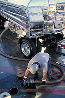 Worker unloading fuel truck to underground storage tank