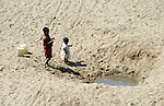 TANZANIA children at water hole in dry river bed in Meatu district / TANSANIA Meatu Kinder an einem Wasserloch in ausgetrocknetem Fluss