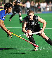 NZ's Steve Edwards flicks the ball past Jivan Mohan during the international hockey match between the New Zealand Black Sticks and Malaysia at Fitzherbert Park, Palmerston North, New Zealand on Sunday, 9 August 2009. Photo: Dave Lintott / lintottphoto.co.nz