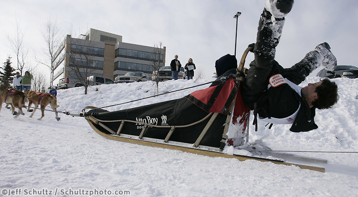 Steve Madsen of Cougar, Washington does a gymnast twist on his sled as his team runds down the trail in Midtown Anchorage during Saturday's ceremnial start in Anchorage.